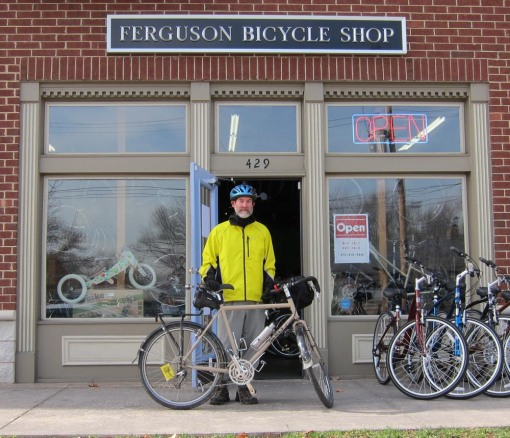 A then-bearded Gerry Noll posing outside his Ferguson Bicycle Shop on November 15, 2012, after being photographed bicycling past new BMUFL sign at south end of Ferguson-controlled Florissant Rd.