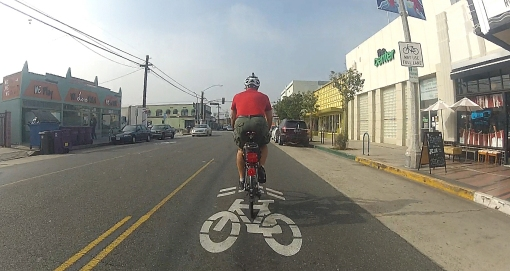 "Dan Gutierrez demonstrating preferred lane position and location of ""effective lane"" centered sharrows on 4th St., Long Beach, CA, in 2012.  Photo: Dan Gutierrez"